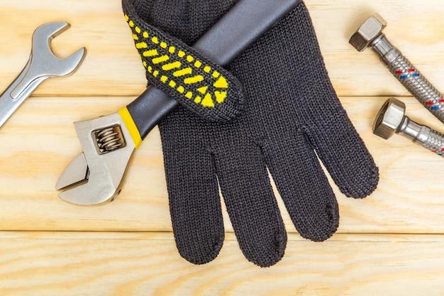 Herramientas de reparación de equipos de fontanería llave ajustable y guantes, conexión flexible sobre tablas de madera