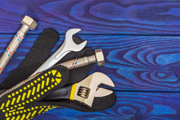 Herramientas de reparación de equipos de fontanería llave ajustable y manguera, guantes, conexión flexible en tableros azules