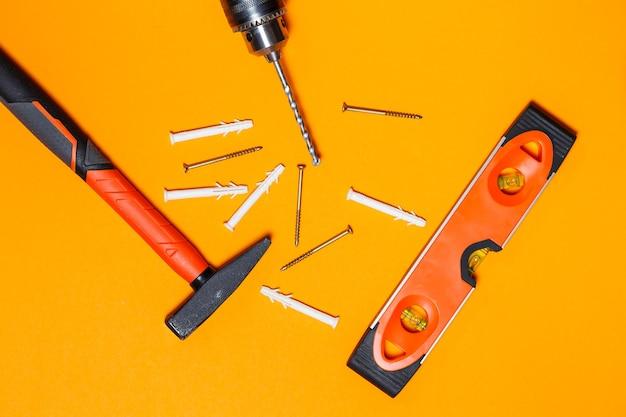 Herramientas para reparaciones de uso doméstico. martillo para clavos, nivelar y taladrar, clavija en la pared sobre fondo naranja. kit de herramientas para el asistente