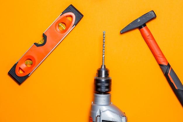 Herramientas para reparaciones de uso doméstico. martillo para clavos, nivelar y taladrar sobre fondo naranja. kit de herramientas para el asistente