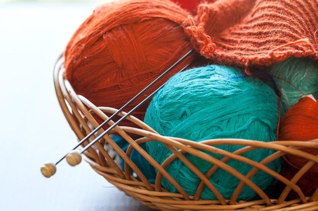 Herramientas de tejido y bolas de hilo en una canasta