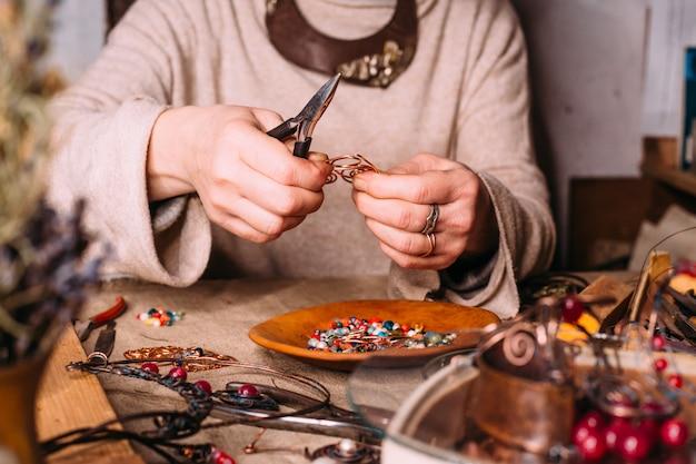 Herramientas de trabajo de alambre de cobre hechas a mano sobre la mesa con accesorios. concepto de arte de personas artesanales