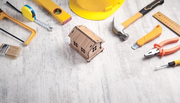 Herramientas de trabajo con un modelo de casa de madera.