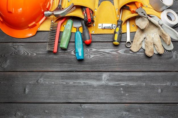 Herramientas de trabajo surtidas en mesa de madera.
