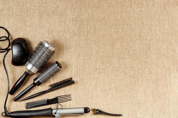 Herramientas vista superior de peluquería sobre un fondo beige.