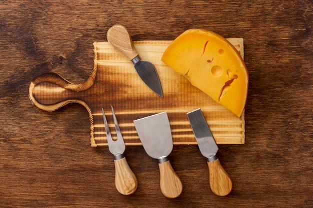 Herramientas de vista superior con una rodaja de queso sobre una mesa
