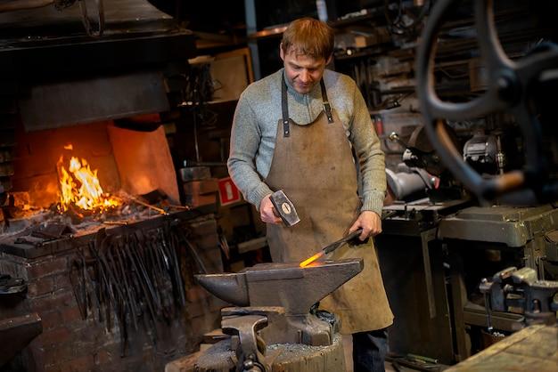 El herrero forja manualmente el metal al rojo vivo en el yunque en herrería con fuegos artificiales de chispa