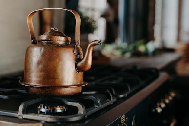 Hervidor de bronce en cocina moderna. tetera de época antigua en la estufa de gas. preparando té. tetera de aluminio. luz del día soleada desde la ventana.