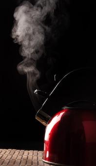 Hervidor rojo saliendo del humo sobre una estera de madera