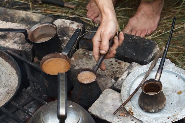 Hervir café en cezva turca en una parrilla sobre una hoguera encendida, un concepto de campamento