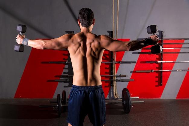 Hexágono pesas hombre entrenamiento vista trasera en el gimnasio