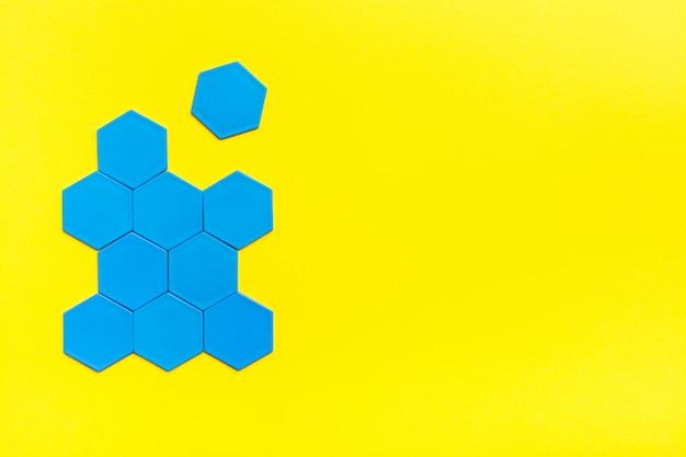 Los hexágonos azules forman una colmena sobre un fondo amarillo. un hexágono está separado de la figura. el concepto de suspensión. copia espacio