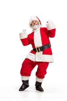 Hey hola. holly jolly x mas festive noel. longitud total de santa feliz divertido en sombreros, traje, cinturón negro, guantes blancos, olas con la palma del brazo de pie en el estudio sobre fondo blanco