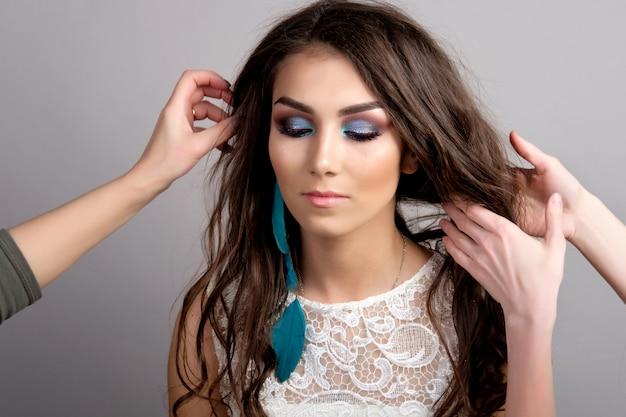 Hiair estilista haciendo un tocado para novia joven, estudio, fondo gris