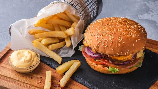 Сhicken hamburguesa papas fritas en una tabla de madera.