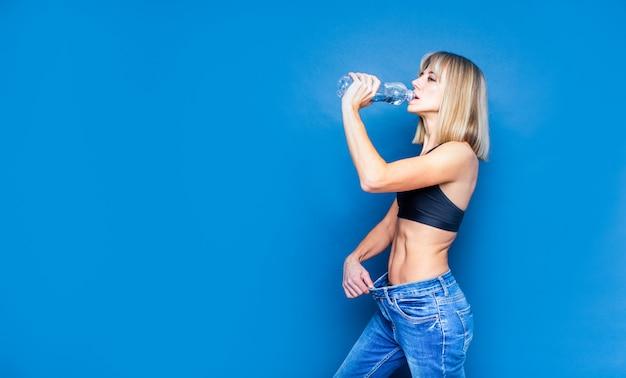 Hidratación, dieta saludable, concepto de bebida. el agua potable de la mujer de una botella y sostener los pantalones grandes la puso, tiro del estudio en el espacio azul, copyspace.