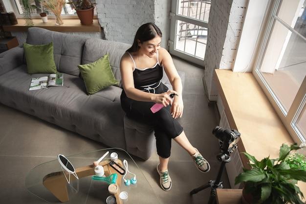 Hidratante. la mujer caucásica bloguera hace vlog cómo ser positivo para el cuerpo y tomar un tratamiento de belleza. usando cámara, grabando su prueba de cosméticos, tutoriales.