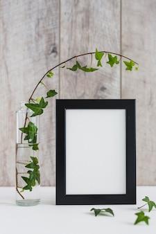 Hiedra en florero de vidrio y marco de fotos blanco en escritorio contra pared