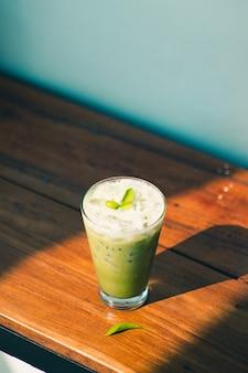 Hiele el té verde o el café con leche del macha en los vidrios altos en la decoración de madera blanca de la tabla y de la ropa objeto.