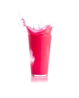 Hielo cayendo dentro de un vaso con bebida rosa