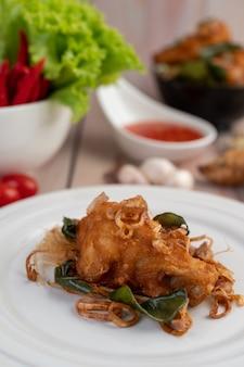 Hierba pollo frito en un plato blanco sobre un piso de madera.