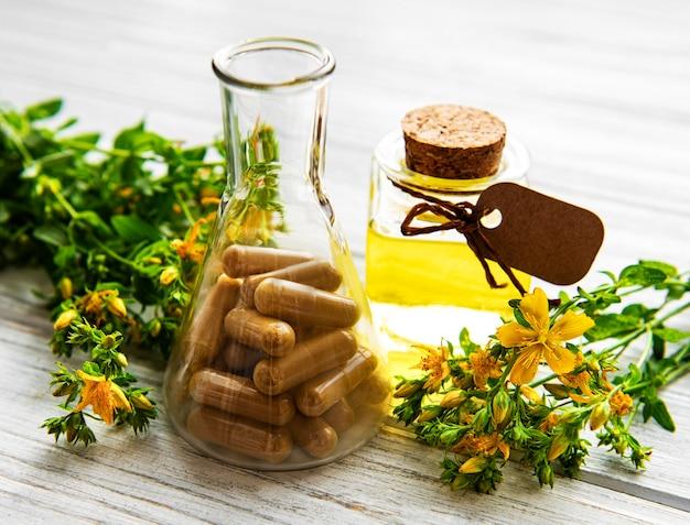 Hierba de san juan, píldoras médicas a base de hierbas en tubo de ensayo, botellas con aceite natural