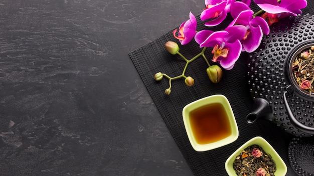 Hierba de té seca y flor de orquídea rosada con tetera en superficie negra