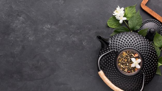 Hierba de té seca con tetera negra y flor de jazmín blanca sobre fondo de piedra pizarra