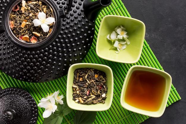 Hierba del té en un tazón de cerámica y tetera en mantel verde sobre fondo negro