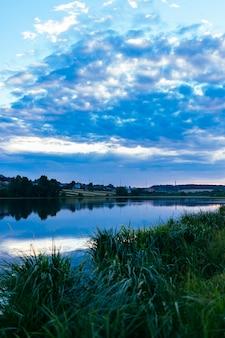 Hierba verde sobre el idílico lago con cielo azul dramático