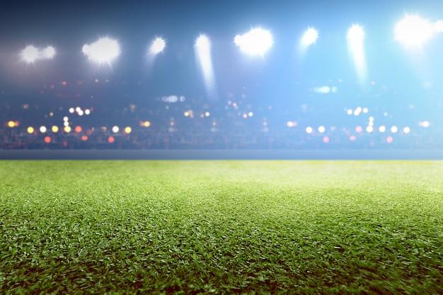 Hierba verde y tribuna con luces borrosas