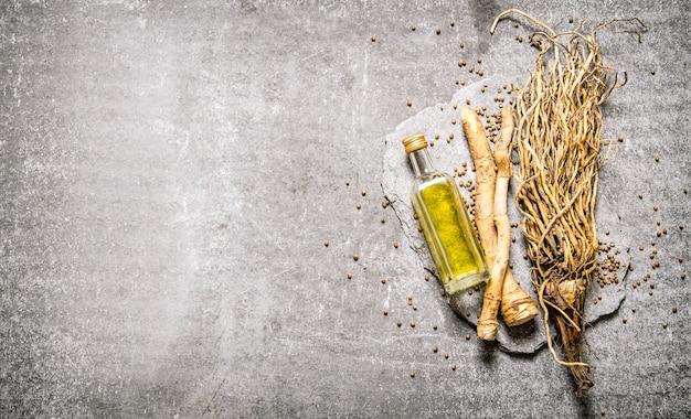 Hierbas con aceite de oliva en una botella sobre piedra de pie sobre la mesa de piedra. vista superior