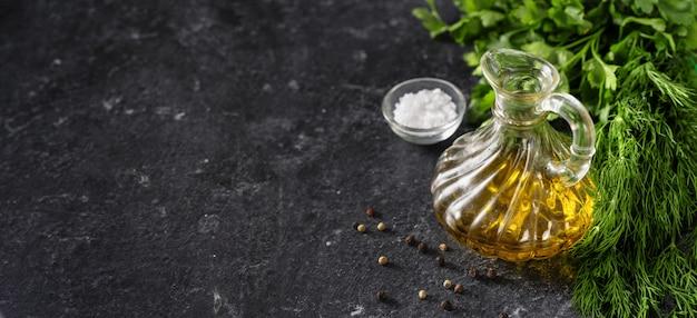 Hierbas, aceite de oliva y sal sobre fondo negro