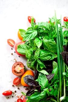 Hierbas aromáticas frescas verdes - tomillo, albahaca, perejil en fondo gris. marco de alimentos, diseño de la frontera.