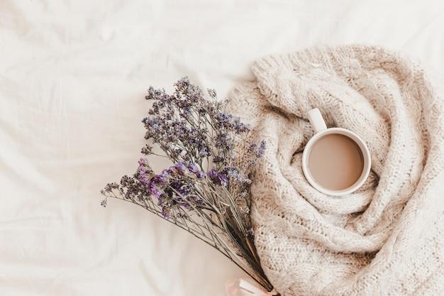 Hierbas cerca de la bebida caliente en cuadros en sábana
