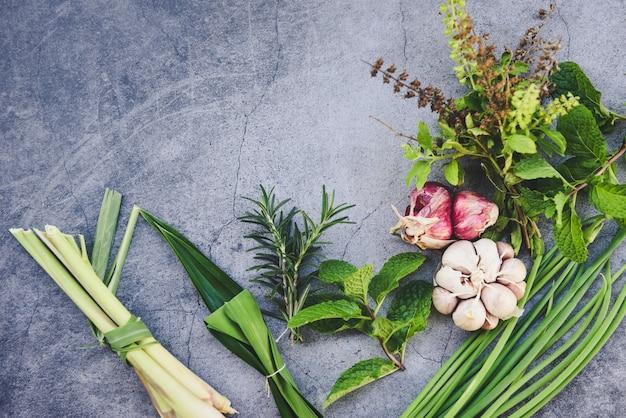 Hierbas y especias frescas naturales en un plato negro en la cocina para ingredientes alimenticios - concepto de jardín de hierbas de cocina