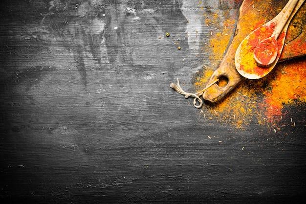 Hierbas y especias indias molidas en cucharas