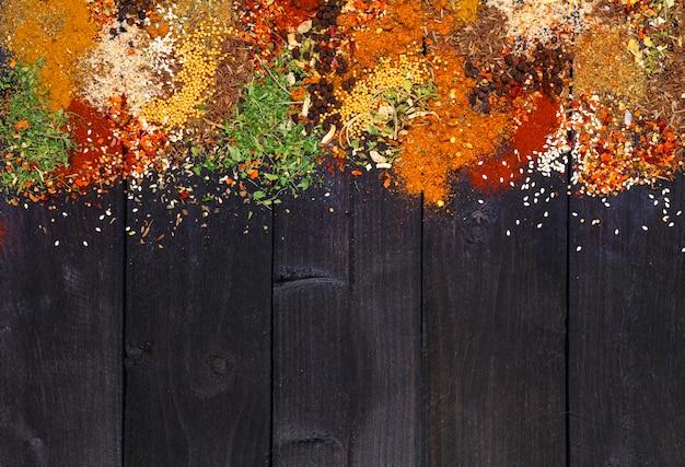 Hierbas y especias sobre superficie de madera negra
