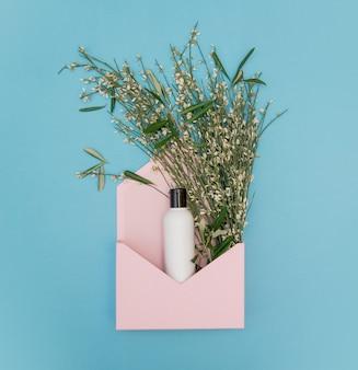 Hierbas, flores y botella de crema en sobre rosa sobre fondo azul. vista superior