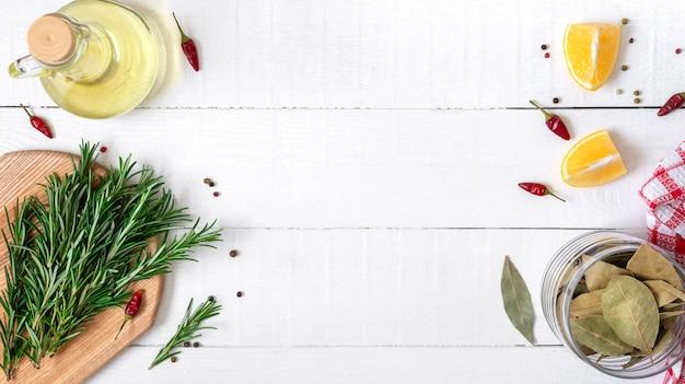 Hierbas frescas, especias, limón y aceite de mesa de madera blanca. fondo de comida