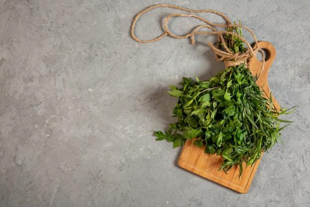 Hierbas frescas superiores en tabla de cortar de madera en gris