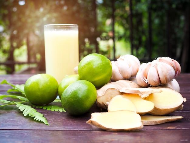 Hierbas medicinales con lima limón, jengibre, ajo y vaso de jugo extraído de hierbas en mesa de madera.