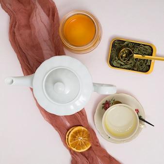 Hierbas; rodajas de limón seco; tetera; tarro de miel con tela textil marrón sobre el fondo de hormigón