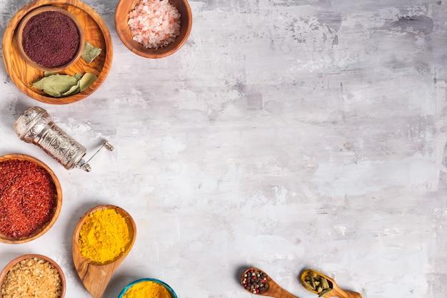 Hierbas secas y alimentos de especias en cucharas y cuencos en piedra como marco, plano