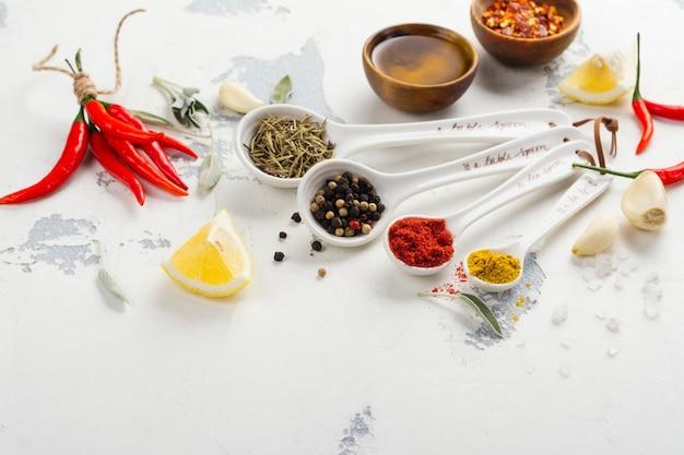 Hierbas secas y especias en cucharas de medir en la mesa de la cocina de piedra blanca