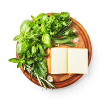 Hierbas en la tabla de cortar albahaca fresca perejil salvia menta romero racimo y libro de recetas