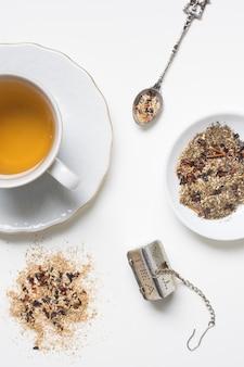 Hierbas con taza de té; cuchara y colador sobre fondo blanco.