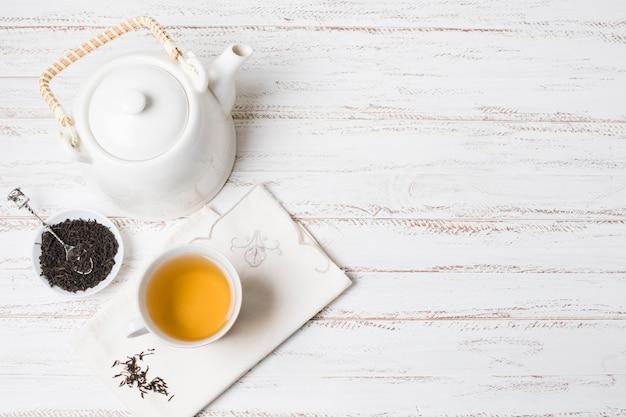 Hierbas y taza de té con tetera en escritorio de madera con textura blanca