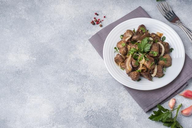 Hígado de pollo al horno con cebolla en un plato.