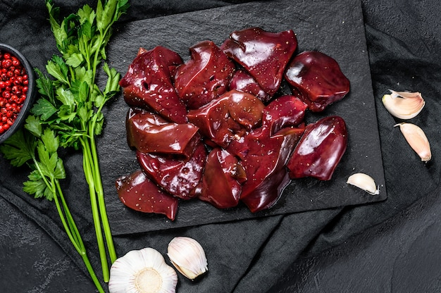 Hígado de pollo crudo en un tablero de piedra. fondo negro. vista superior